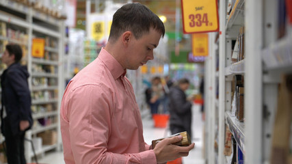 young guy buys coffee beans in a store or supermarket.
