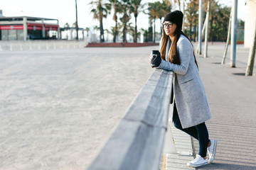 Woman holding a coffee thermos by the beach on winter.