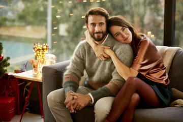 Loving Young Woman Embracing Man On Sofa During Christmas