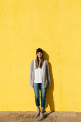 Portrait of a woman standing in front of a yellow wall.