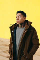 Portrait of an asian tattooed man standing in front of a yellow wall.