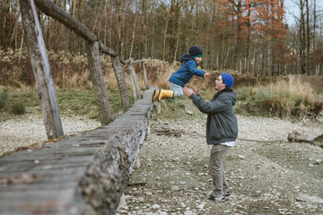 young boy jumping off a small wooden bridge to his big brother