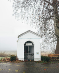Tiny chapel entitled to Holy Mary under leafless tree in italian countryside