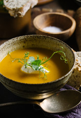 A bowl of carrot soup in a rustic setting.