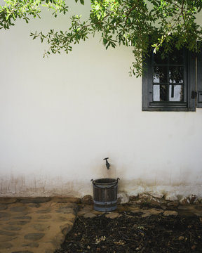 Farmhouse Hotel wooden water bucket and faucet under front window on a white wall