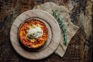 Lasagna meal in the rustic plate on wooden pad