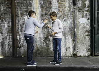 Young handsome boys play on curb in an old tunnel