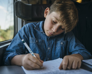 Young boy writing a letter while travelling in train