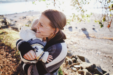 Young mom enjoying hugging with son outside at the beach