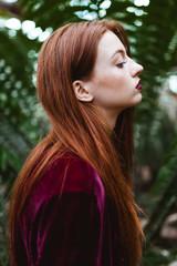 Beautiful redhead in a greenhouse