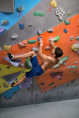Young man rock climbing an artificial wall