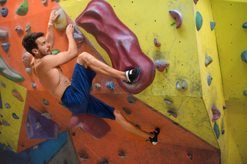 Young man free climbing indoor
