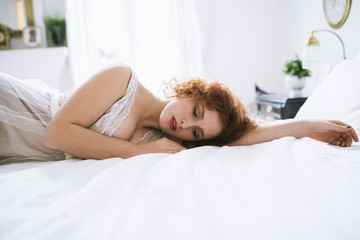 Beautiful ginger haired woman lying on a bed