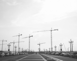 Construction cranes towering above urban street and walkway