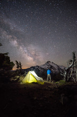 Man standing watch in front of Mt Jefferson with starry night sky