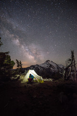 Man in tent in front of Mt Jefferson with starry night sky