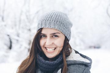 Portrait of happy woman wearing knit hat in snowy field