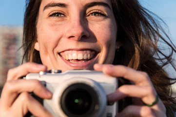 Caucasian woman smiling and taking pictures outdoors