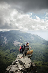 Man sitting on cliff up high overlooking forests