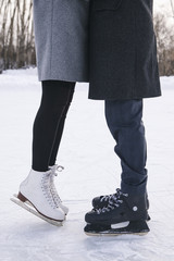 Close-up of young couple's legs on ice rink
