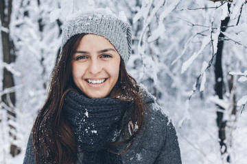 Portrait of happy woman wearing knit hat in snowy field