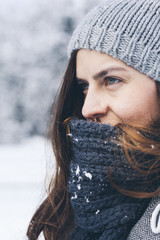 Young woman wearing knit hat in snowy field