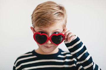 cute boy looking over valentine's sunglasses