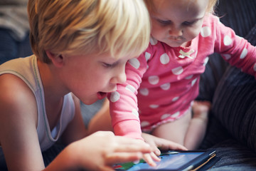 Two children using a digital tablet