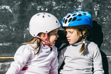 Two Sisters Having a Break During a Rollerblading Exercise