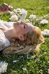 Beautiful blonde woman lying on green grass and smelling white flowers