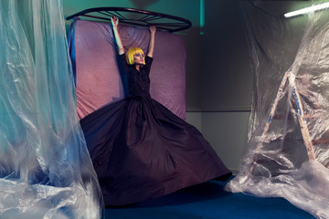 A beautiful model with a haute couture dress in a moody room