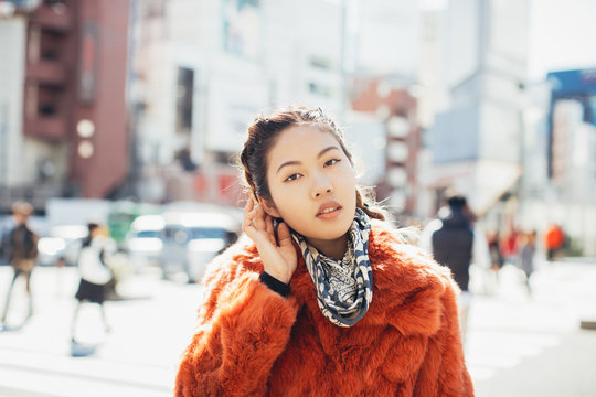 Outdoor Portrait of Young Pretty Asian Woman in Red Fur Coat Touching Her Head