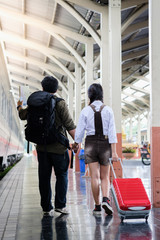 Woman and man hold hands walk in train station go travel drag bag red color,man holding map