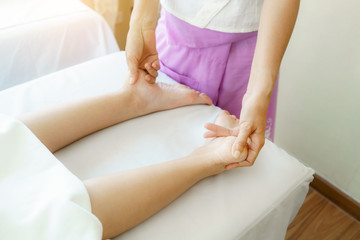 Female professional massager 's hands pressing client's feet for Thai traditional massage in Spa salon