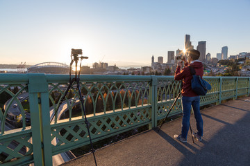 Seattle Downtown, Washington, USA - April 15, 2017 - Photographer taking pictures of Downtown Seattle City Skyline from a popular location on Dr Jose P Rizal Bridge during sunset..