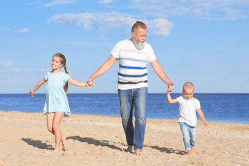 Cute children with grandfather on sea beach