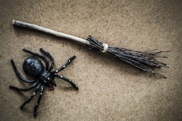 Witch's broom with spider on the floor. Traditional Halloween symbol. Ancient natural, old wooden broom created from tree branches, which wiped rooms, yards and streets. Retro vintage style.