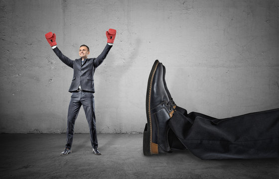 A happy businessman with boxing gloves on arms raised in victory stands near a giant male leg fallen down.