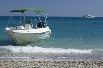 Moored boat on the beach of Kolymbia and the walking yacht in the Mediterranean Sea (Rhodes, Greece).