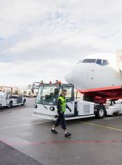 Worker Walking By Truck Towing Airplane On Runway