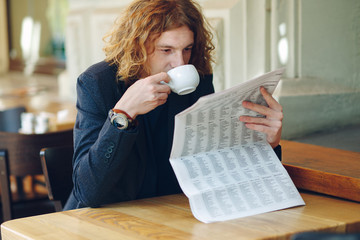 Hipster man drinking coffee while reading