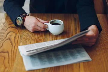 Man's hands close-up holding cup of coffee and a newspaper