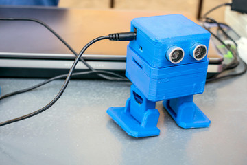Funny blue robot printed on a 3D printer. Toy cute automatic robots are dancing on the table. Selective focus