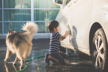 asian child washing a car on summer day