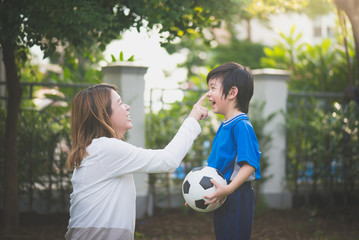 Asian mother and son Playing Soccer