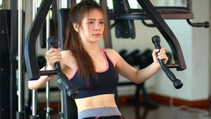 Fitness woman workout on chest press machine in sport club