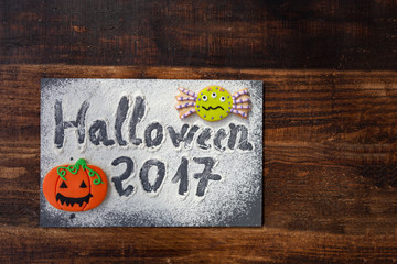 "SThe words ""Halloween 2017"" on a slate with flour and cookies"
