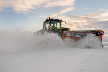 Traktor mit Schneepflug bei der Schneeräumung in Österreich. Landwirtschaftlich ausgerichtete Betriebe nutzen den Winter um Ihre Maschinen besser auslasten zu können.