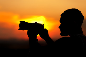 Silhouette of young man with camera at sunset time