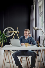 Businessman using smart phone for business talk and sitting at home office